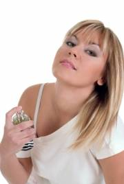 Blonde Frau, die sich Parfüm auf den Hals sprüht