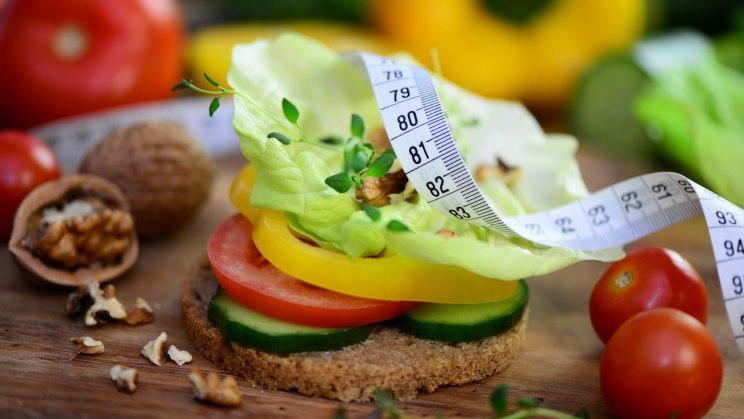 Gesunde Ernähruing hilft beim Abnehmen. Gemüse mit einem Maßband dekoriert.
