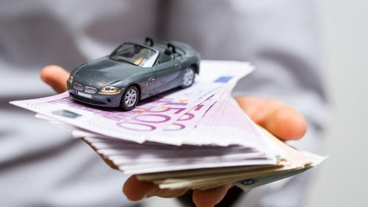 Wann soll man ein Auto kaufen? Auf dem Bild steht ein Spielzeugauto steht auf einem Bündel Euroscheine