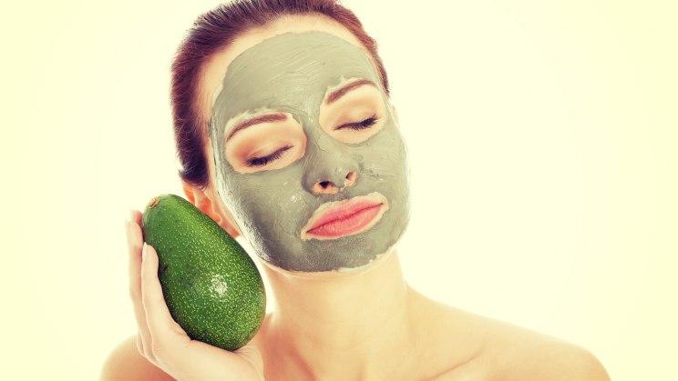 Frau hat eine Avocado-Gesichtsmaske aufgetragen