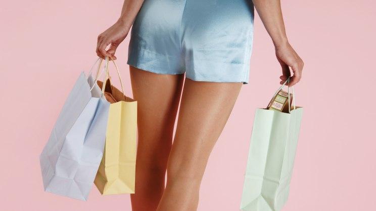 Eine Frau in Shorts mit bunten Einkaufstüten