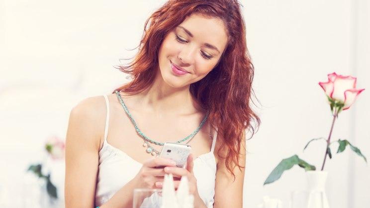 Eine hübsche junge Frau am Telefon telefoniert nach dem ersten Date.