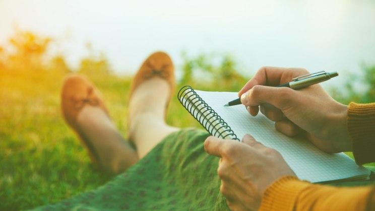 Handschrift, eine Frau sitzt auf einer Wiese und schreibt estwas auf einen Block.