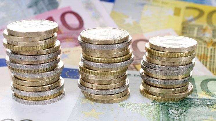 Wieviel bleibt nach Steuer? Mehrere Stapel 1-Euro-Münzen auf Euroscheinen gestapelt.