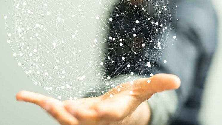Ein Mann hält ein netzwwerkartiges rundes Objekt in der Hand. Alle Teile sind miteinander verbunden.