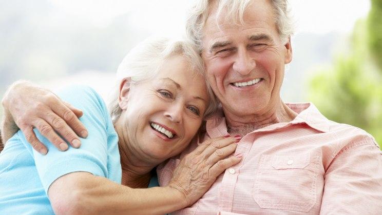Ein glückliches älteres Paar strahlt in die Kamera.