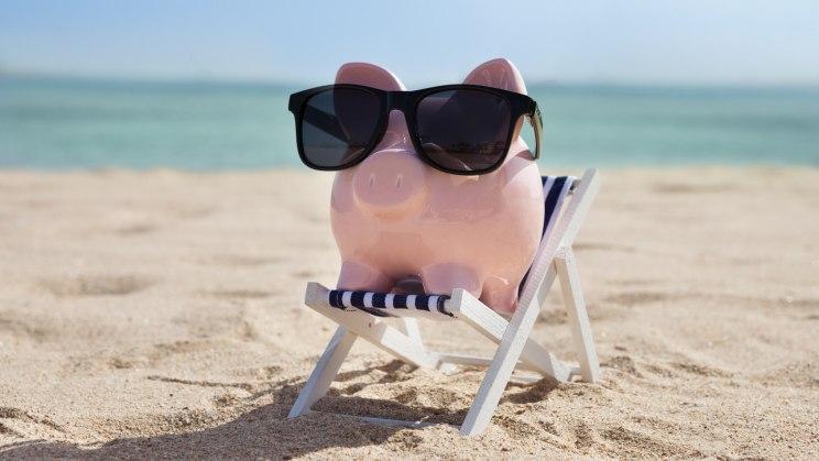 Ein Sparschwein auf einem Liegestuhl am Strand