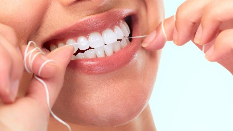 Frau reinigt mit Zahnseide die Zahnzwischenräume