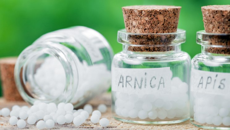 Arnica-Globuli in Glas: Arnica montana wirkt bei Insektenstichen