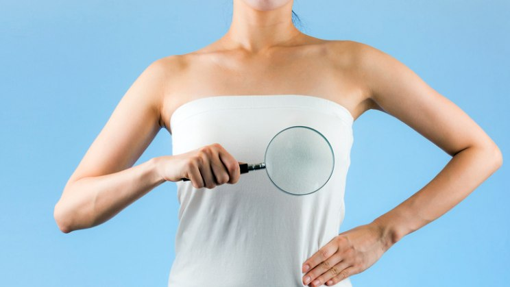 Frau mit Lupe: Knoten in der Brust als Anzeichen für Brustkrebs