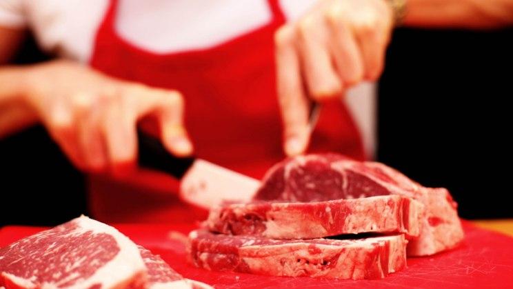 Frau schneidet Fleisch: Fleisch und Wurst nur sparsam genießen