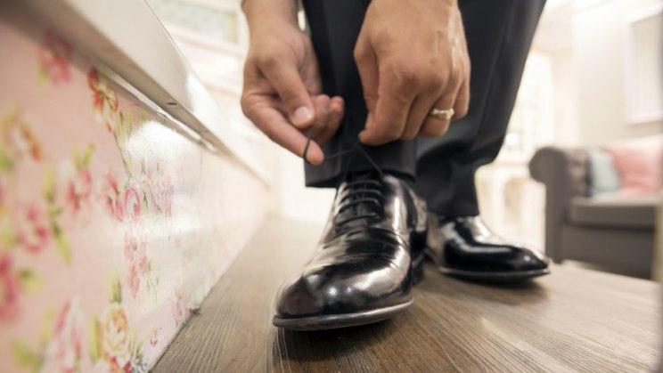 Mann bindet Lederschuh: Atmungsaktives Schuhwerk gegen Fußpilz