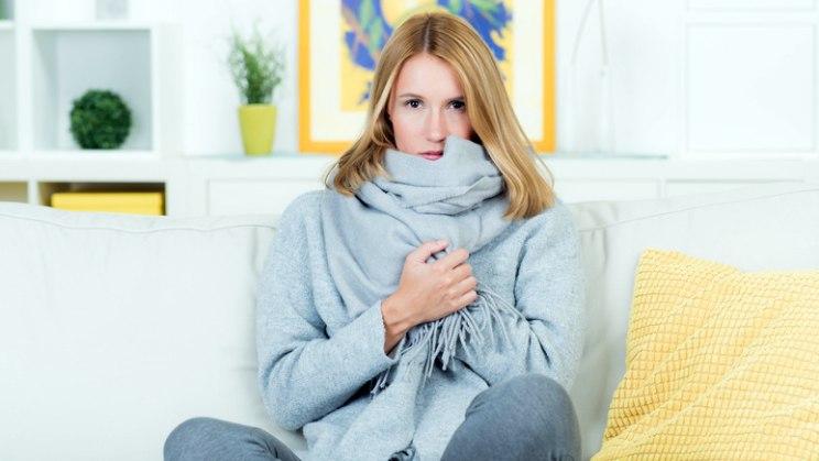 Frau auf Sofa mit Schal: Bei Halsschmerzen den Hals warm halten!