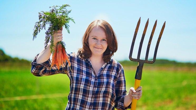 Frau mit Karotten und Mistgabel: Obst und Gemüse am besten saisonal und regional