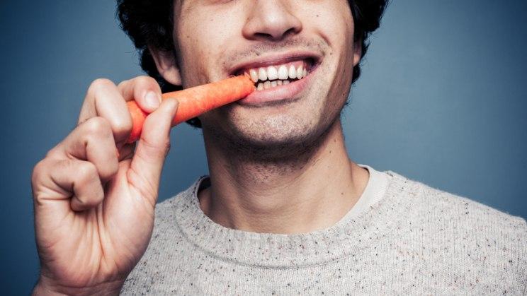 Mann mit Karotte: Carotinoide stecken in Karotten