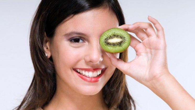 Frau mit Scheibe Kiwi: Vitamin C hilft beim Kalorien verbrennen