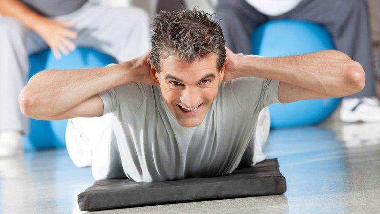 Mann bei Gymnastik: Rückenschule hält den Rücken fit