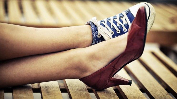 Frau mit High Heel und Turnschuh: Falsches Schuhwerk strapaziert die Fußgelenke