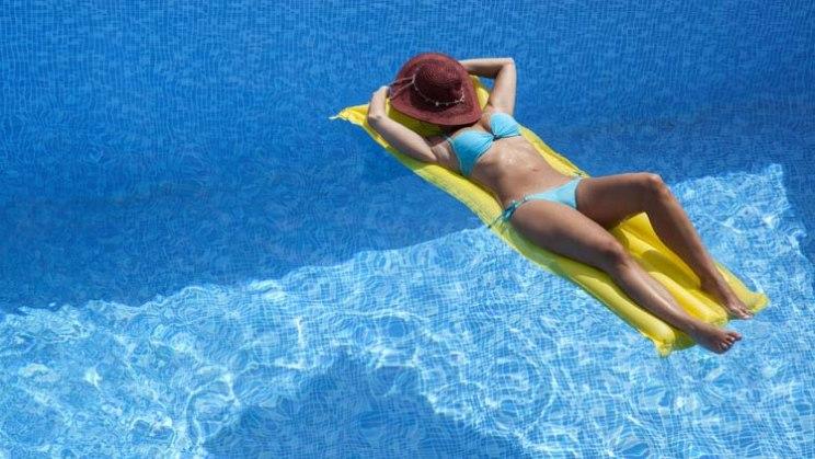 Frau sonnt sich im Schwimmbad: Nicht nur vor dem Schwimmen eincremen