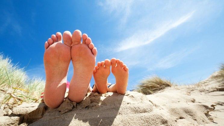 Füße am Strand: Vitamin-D-Speicher im Sommer gut auffüllen