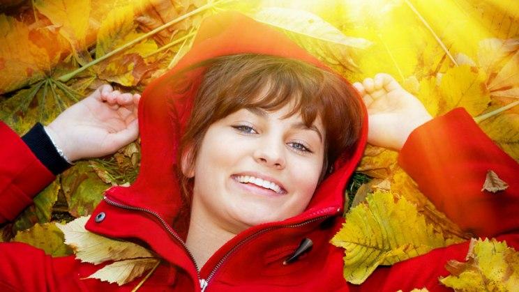 Frau liegt in der Herbstsonne: Gesicht und Hände für die Vitamin-D-Produktion frei lassen