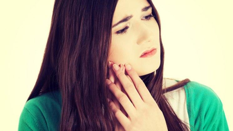 Frau mit schmerzender Backe: Aphthen im Mund können ziemlich schmerzhaft sein