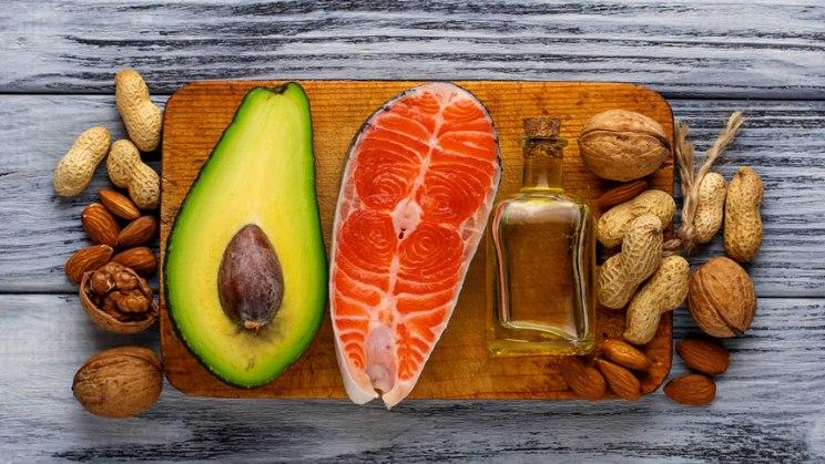 Brett mit Lachs, Nüssen und Avocado: Gesunde Ernährung senkt den Cholesterinspiegel