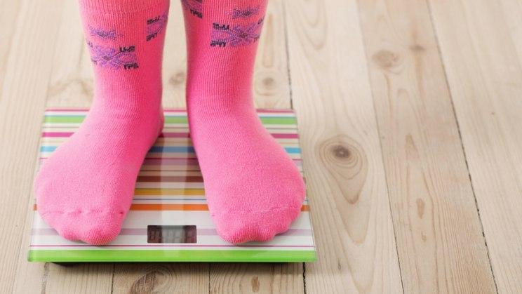 Kind auf Waage: Wer als Kind gehänselt wird, bleibt oft langfristig dick