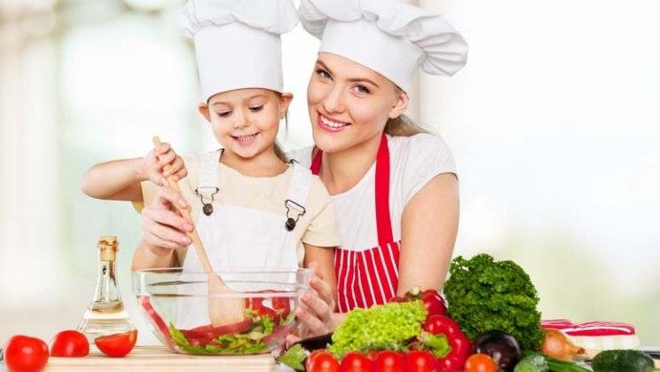 Frau mit Kind beim Kochen: Ein Eisenmangel lässt sich durch ausgewogene Ernährung verhindern