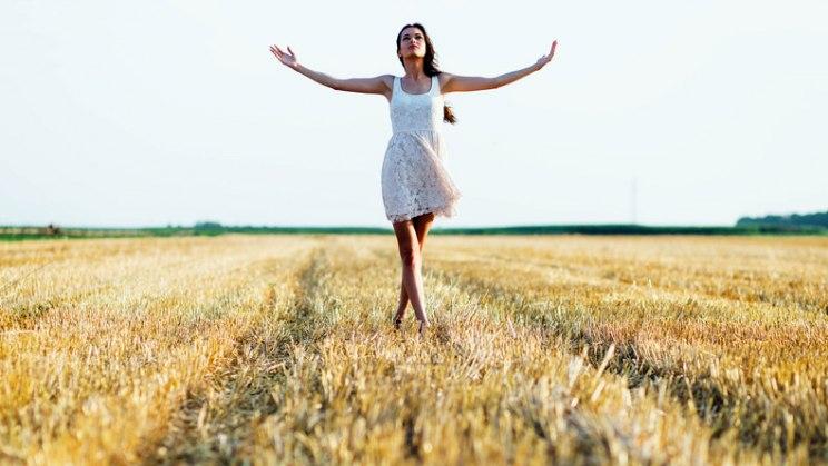Entspannte Frau auf Feld: Entspannungsübungen bremsen den Schmerz