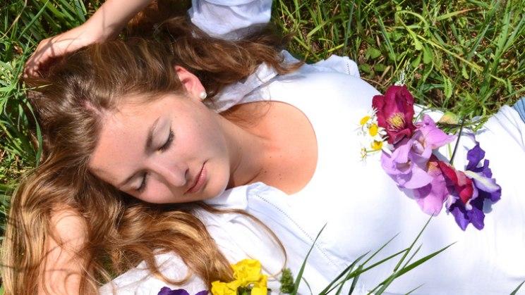 Schlafende Frau in Wiese: Frühjahrsmüdigkeit durch die Wetterumstellung?