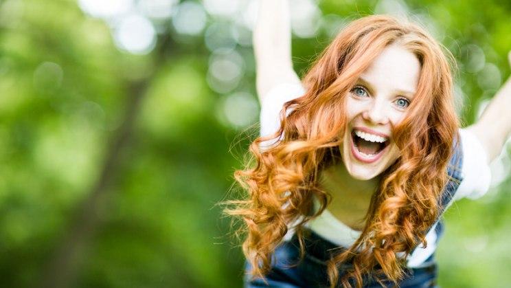 Frau freut sich: Glück kann Symptome wie bei einem Herzinfarkt auslösen