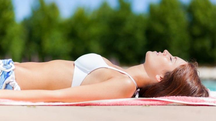 Frau beim Sonnenbad: Hautkrebsrisiko steigt durch UV-Strahlung