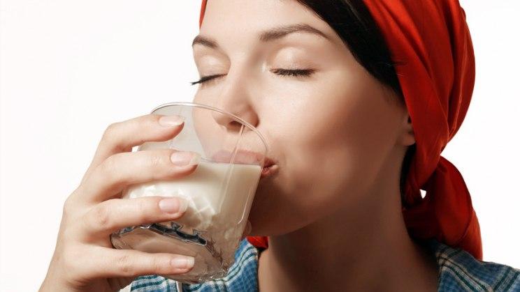 Frau trikt Glas Milch: Kalzium ist vor allem in Kuhmilch enthalten
