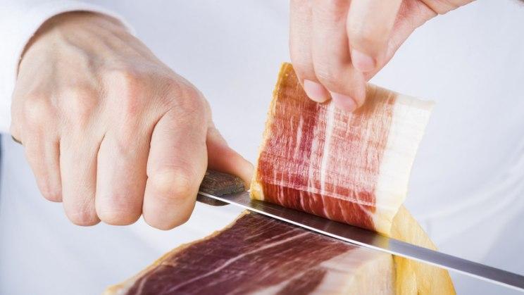 Mann schneidet Schinken: Schinken- und Wurstwaren können mit Listerien verunreinigt sein