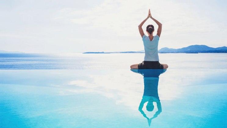 Frau beim Yoga am Strand: Yoga lindert Symptome der Multiplen Sklerose