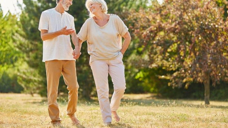Glückliches, älteres Pärchen beim Spazierengehen: Wie es mit dem Liebesspiel im Alter klappt.