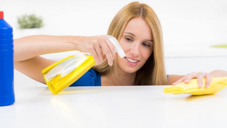 Frau putzt mit Badreiniger: Die Gefahr für ein toxisches Kontaktekzem besteht beim Kontakt mit Putzmitteln.