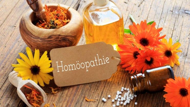 Blüten, Globuli und Co. auf einem Tisch: Homöopathie kann bei einer Kontaktallergie angewandt werden.