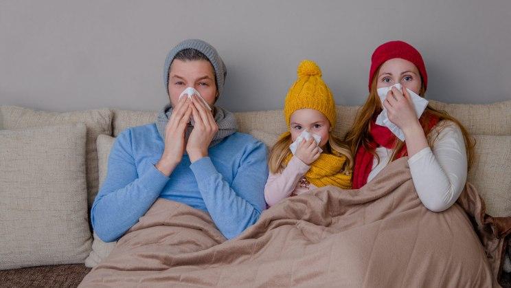 Vater, Mutter und Kind haben Schnupfen und liegen im Bett.