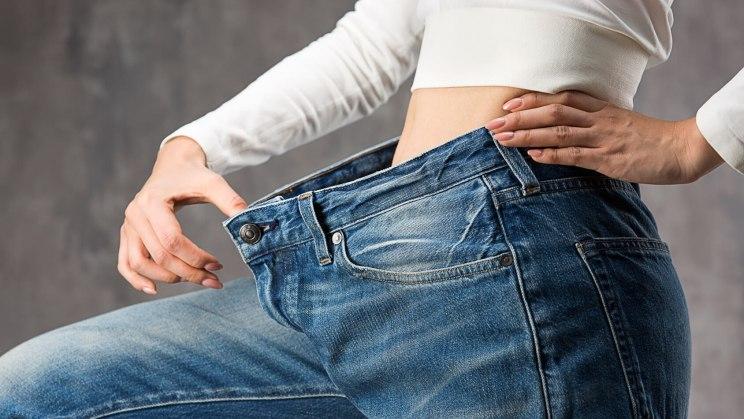 Einer Frau passt nach dem Abnehmen ihre Jeans nicht mehr.