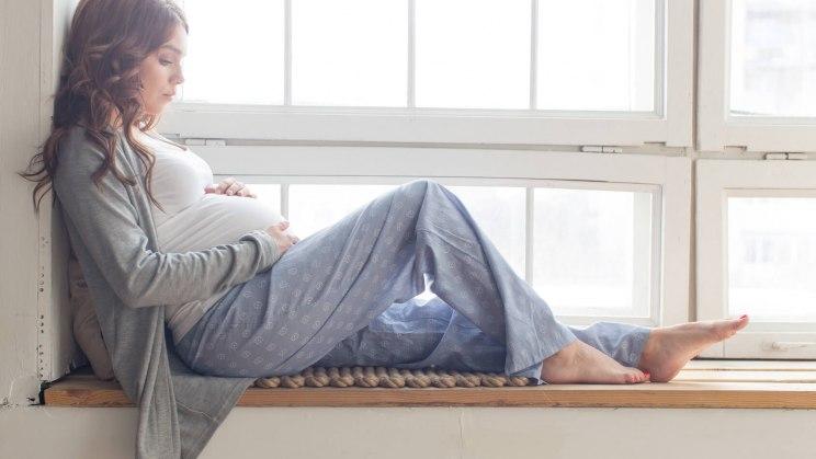 Schwangere Frau sitzt vor dem Fenster und sorgt sich um Komplikationen in der Schwangerschaft