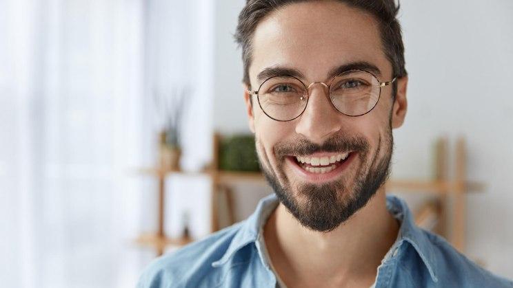 Strahlender junger Mann: Dank einer schicken Brille wird seine Hornhautverkrümmung ausgeglichen.