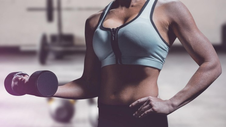 Eine Frau trainiert ihre Arme gemäß dem neuen Fitnesstrend: strong is the new skinny.