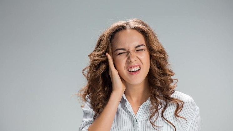 Eine junge Frau fasst sich mit schmerzverzerrtem Gesicht ans Ohr, weil sie einen Tinnitus bedingt durch Stress hat.
