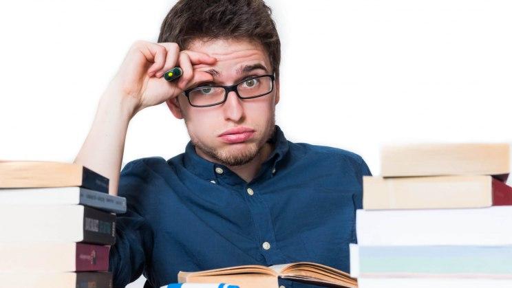 Eine Tasse Tee steht zum Bewältigen von Prüfungsstress vor einem Studenten, der sich die Hände an den Kopf hält.