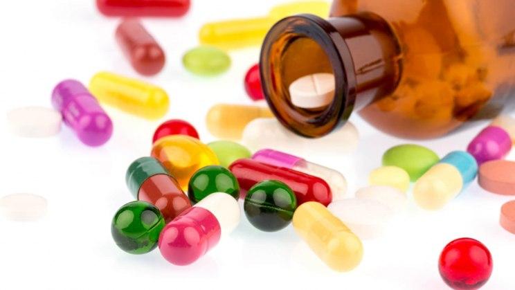 Viele bunte Pillen, von denen einige zur Medikamentensucht führen, liegen auf einem Tisch verteilt.