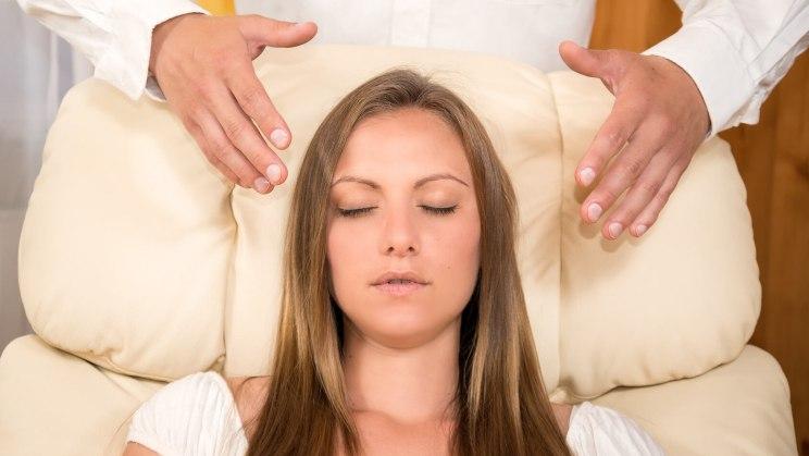 Eine prüfungsstressgeplagte Frau entspannt während ihrer Stresstherapie in einem Sessel.