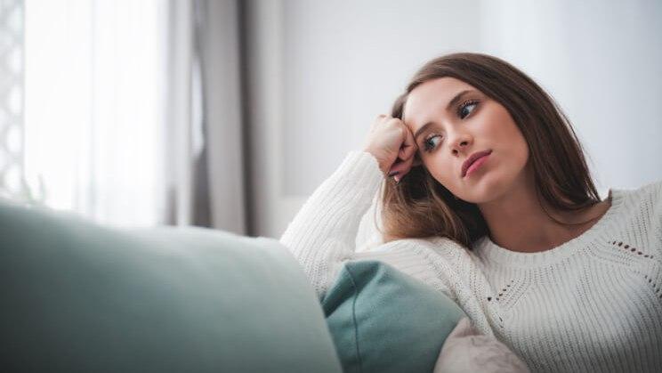 Alt-TagFrau sitzt auf der Couch, weil sie ihre Vitamine gegen Erschöpfung vergessen hat.
