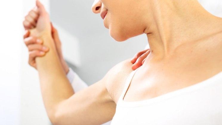 Eine Frau mit starken Knochen hebt ihren Arm